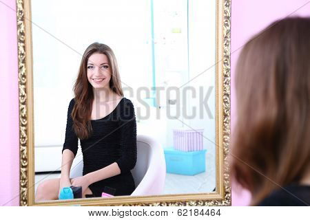 Young beautiful woman sitting front of mirror in room