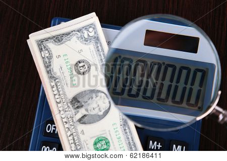 Fraud concept with magnifier and calculator, on wooden background