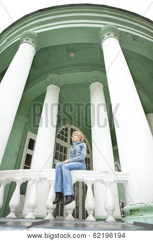 city ??girl sitting on parapet of building with white columns