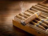 image of cigar  - smoking cuban cigar over box  on wood background - JPG