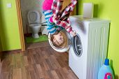 stock photo of button down shirt  - Girl with shirt upside down holding a washing machine at inverted house - JPG