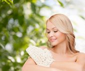 health, spa and beauty concept - smiling woman with exfoliation glove