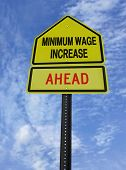 conceptual sign with words minimum wage increase  ahead over blue sky