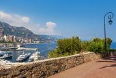 pic of hercules  - Sidewalk with ornate lamppost and view over port Hercules and buildings of Monte Carlo - JPG