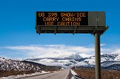 stock photo of hazard  - A lighted message warns travelers to prepare for hazardous driving conditions on a Sierra Nevada mountain road - JPG
