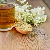 image of meadowsweet  - Wooden spoon with dried flowers a bouquet of fresh flowers of meadowsweet tea in glass mug on the wooden boards - JPG