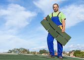 picture of shingle  - Worker putting bitumen shingles on a roof  - JPG