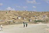 TITANYEN, HAITI - FEBRUARY 11, 2014.  Three Haitians walking up a dusty and rocky road to their hill
