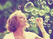 stock photo of hair blowing  - a pretty girl blowing bubbles  - JPG