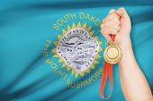 foto of south american flag  - Sportsman holding gold medal with State of South Dakota flag on background - JPG