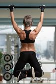 stock photo of pull up  - Female Athlete Doing Pull Ups - Chin-Ups In The Gym ** Note: Shallow depth of field - JPG