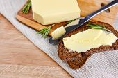 pic of margarine  - Slice of rye bread with butter on wooden cutting board  - JPG