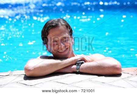 Man Lying On Side Of Swimming Pool In The Sun
