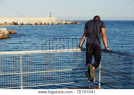 Dark skinned male runner doing pull-ups exercise on beautiful sea background