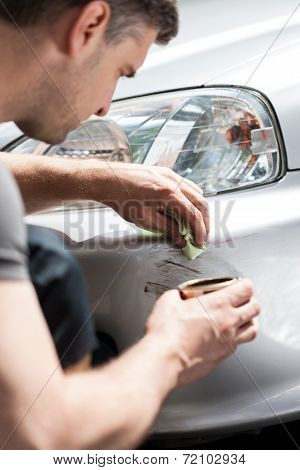 Man Removing Scratches From Car Bumper