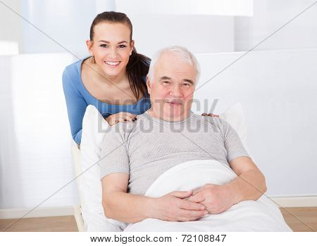 Portrait Of Happy Caregiver With Senior Man