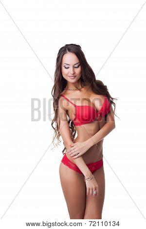 Flirtatious tanned model posing in red lingerie