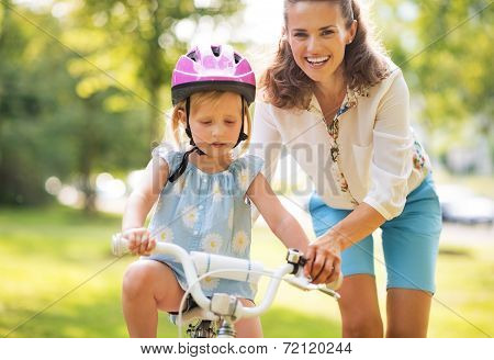 Happy Mother Helping Baby Girl Riding On Bicycle