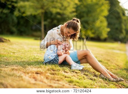 Mother And Baby Girl Sitting Outdoors In The Evening