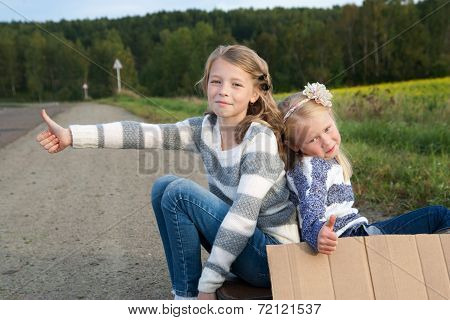 Two girls with suitcase standing about road