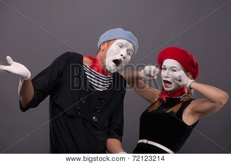 Portrait of sad mime couple crying isolated on grey background