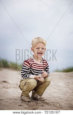 Beautiful boy playing with sand on the beach