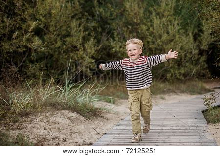 Young boy running with open arms