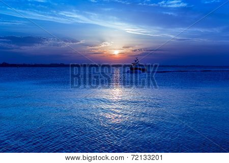 Sunset On The Sea with Sailboat silhouette