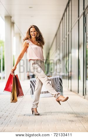 Happy Young Woman With Shopping Bags Rejoicing On The Mall Alley