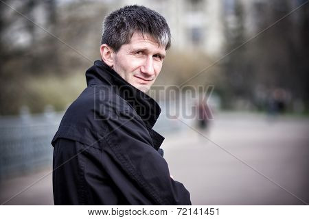 A Man In A Raincoat On The Street