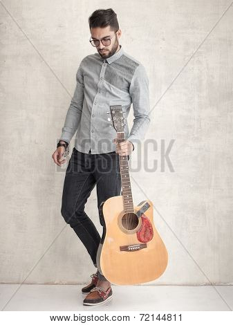 Handsome Man Holding An Acoustic Guitar Against Grunge Wall