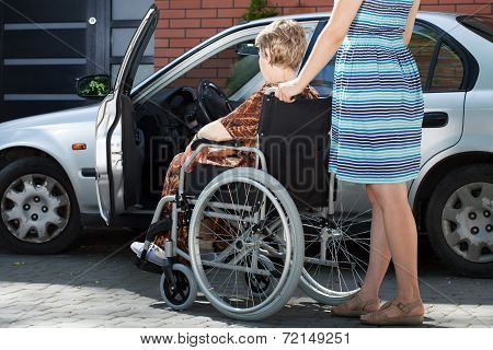 Girl Helping Woman On Wheelchair Getting Into A Car