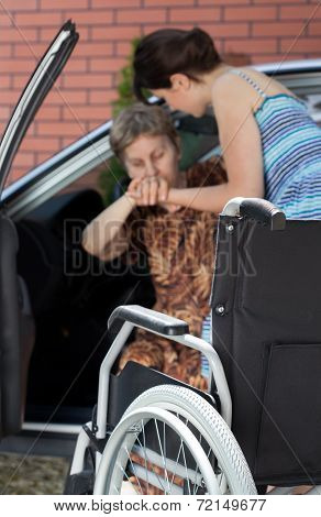 Girl Helping Disabled Woman Coming Out Of Car