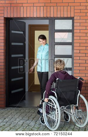 Caregiver Inviting Woman On Wheelchair To Nursing Home