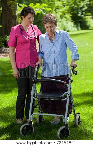 Nurse Walking Beside Woman With Orthopedic Walker