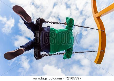 Young Boy Having Fun On A Swing