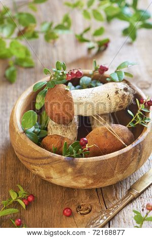 Fresh mushrooms with cranberry in wooden bowl