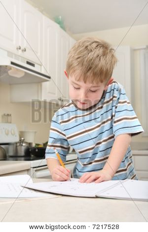 Young Boy Doing Homework In A Kitchen