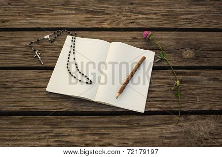 Blank open notebook, wooden pencil and Catholic chaplet with crucifix for pray on wooden backgr