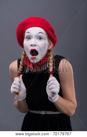 Waist-up portrait of young mime girl showing something