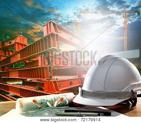 Safety Helmet On Engineer Working Table Against Crane And Road Construction Tool Use For Infra Struc