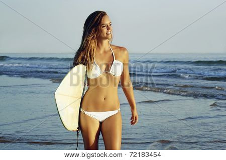 Young beautiful blonde surfer girl walking on beach