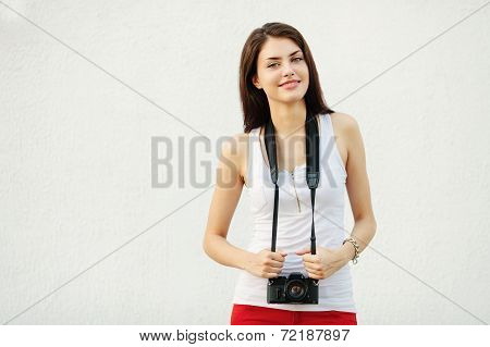 Young happy brunette woman in white t-shirt posing with a photo camera against a white textured wall