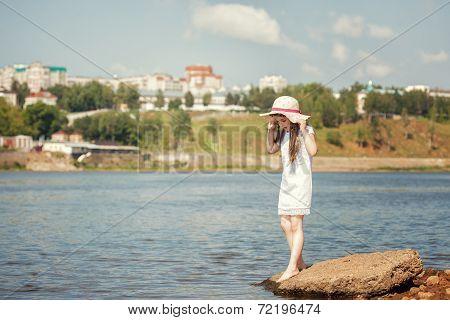 Little fashionista walks along river in park