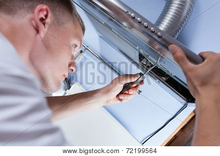 Repairman Mending A Kitchen Extractor