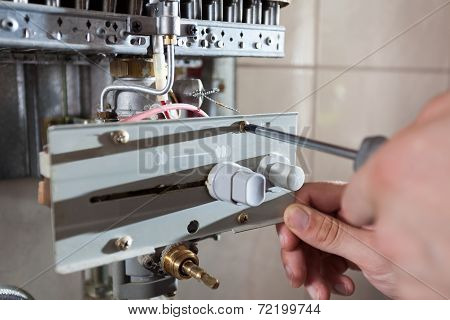Repairman Adjusting Gas Water Heater