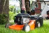 foto of dungarees  - Turning on the lawn mower by gardener