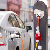 image of electric station  - Power supply for electric car charging.  Electric car charging station. Close up of the power supply plugged into an electric car being charged. ** Note: Soft Focus at 100%, best at smaller sizes - JPG