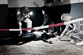 stock photo of crime scene  - A cross processed murder scene with two forensic analysts and a police lieutenant investigating a crime on a businessman in a basement - JPG