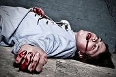 foto of murder  - Murder victim lying on the floor being shot in a basement with blood splatter on the wall - JPG